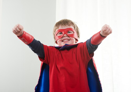 Image of a little boy dressed up like a superhero with a red cape.