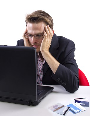 Image of man staring at computer. He looks worried.