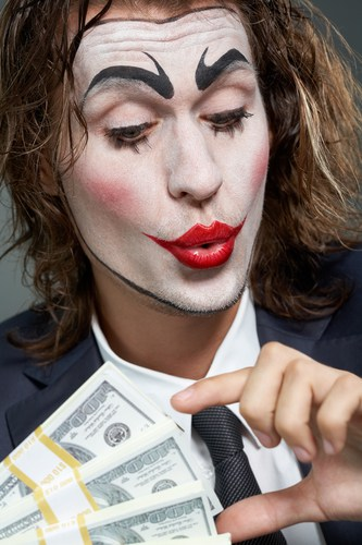 Business man with clown face counting money symbolic of Inbox Dollars unethical business practices.