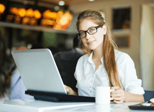 Image of an attractive long hair woman at a laptop. She symbolizes an entrepreneur, someone who is building a legitimate online business by creating value for customers. http://ScamAvenger.com